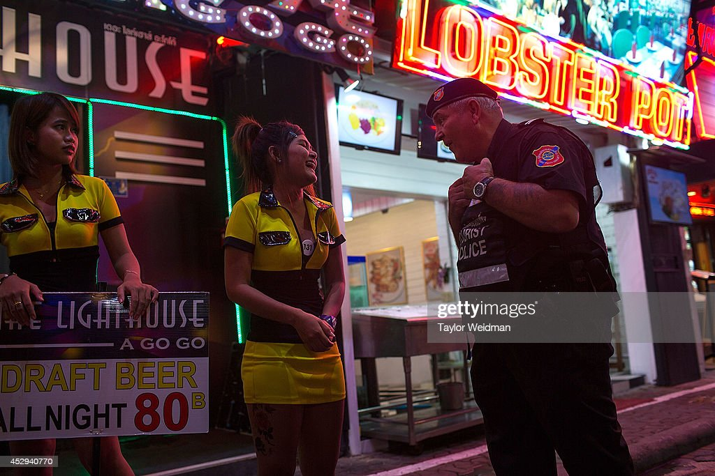 Ray Aldridge, a member of FTPA, chats with an employee of a go go bar on Pattaya's Walking Street on July 30, 2014 in Pattaya, Thailand. Since 2002, members of the Foreign Tourist Police Assistants (FTPA) of Pattaya have been assisting local police on Walking Street, Pattaya's main nightlife area. Members of the FTPA carry handcuffs, batons, and pepper spray, and are charged primarily with assisting foreign visitors and the Thai police, as well as breaking up fights and catching thieves.