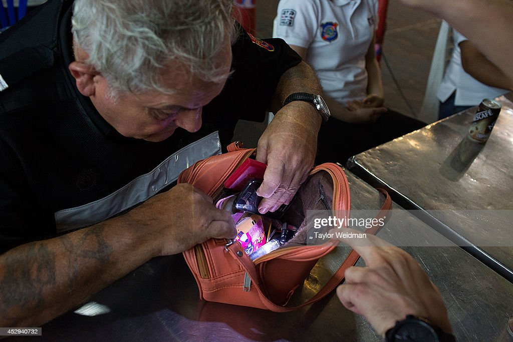 Ray Aldridge, a member of FTPA, searches a Thai woman's purse after a robbery is reported on July 31, 2014 in Pattaya, Thailand. Since 2002, members of the Foreign Tourist Police Assistants (FTPA) of Pattaya have been assisting local police on Walking Street, Pattaya's main nightlife area. Members of the FTPA carry handcuffs, batons, and pepper spray, and are charged primarily with assisting foreign visitors and the Thai police, as well as breaking up fights and catching thieves.