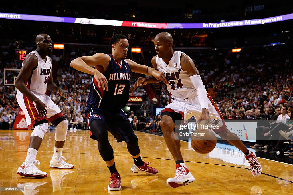 Ray Allen #34 of the Miami Heat drives against John Jenkins #12 of the Atlanta Hawks as Joel Anthony #50 of the Miami Heat looks on at American Airlines Arena on March 12, 2013 in Miami, Florida.