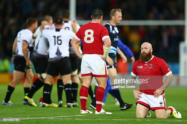Ray Barkwill and Aaron Carpenter of Canada look dejected as Romania players celebrate after the 2015 Rugby World Cup Pool D match between Canada and...