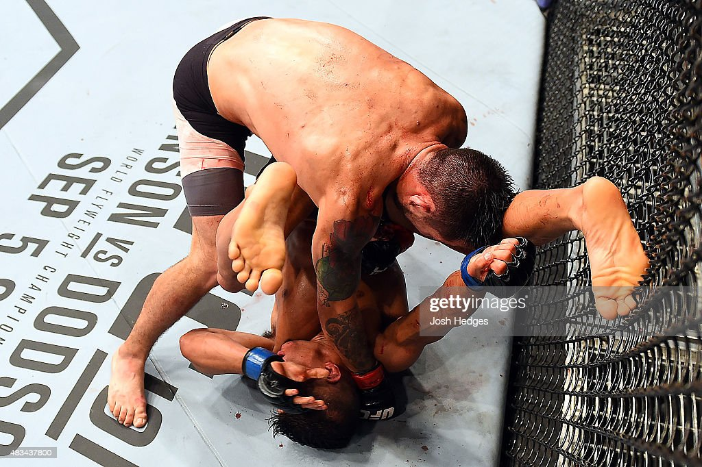 Ray Borg (top) punches Geane Herrera in their flyweight bout during the UFC Fight Night event at Bridgestone Arena on August 8, 2015 in Nashville, Tennessee.