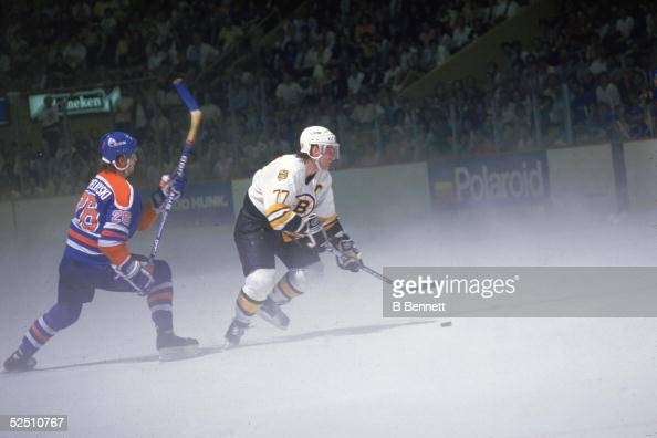 Ray Bourque of the Boston Bruins skates with the puck while Mike Krushelnyski of the Edmonton Oilers pursues him on the ice during Game 4 of the 1988...