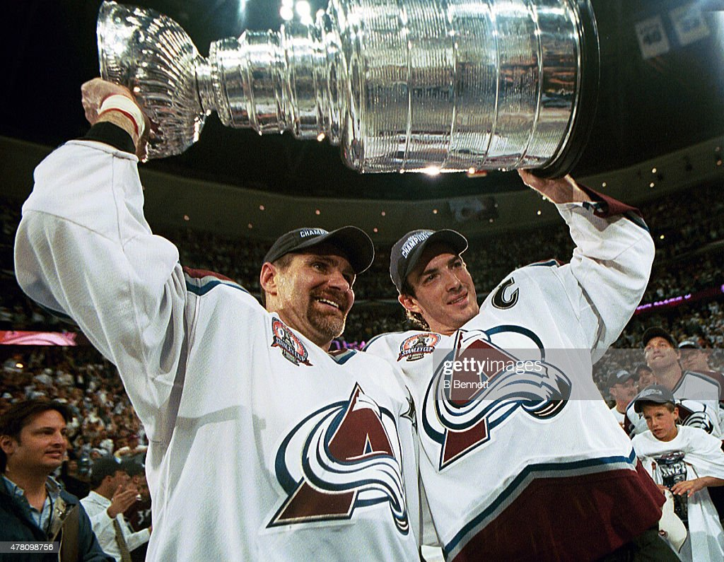 Ray Bourque #77 of the Colorado Avalanche lifts the cup with Joe Sakic #19 after the Colorado Avalanche defeated the New Jersey Devils 3-1 in game seven of the NHL Stanley Cup Finals at Pepsi Center in Denver, Colorado. The Avalanche take the series 4-3.