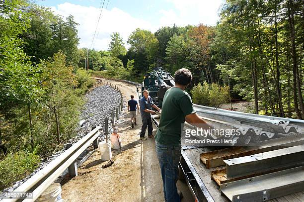 Ray Clark and Derek Alves of Main Line Fence install a guard rail as they and 19 other firms donate labor materials and money to rebuild a private...