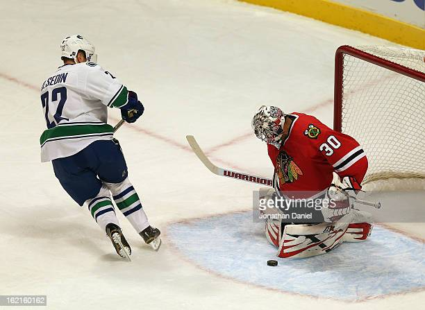 Ray Emery of the Chicago Blackhawks makes a save against Daniel Sedin of the Vancouver Canucks at the United Center on February 19 2013 in Chicago...