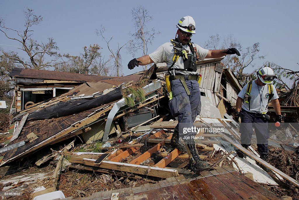 Ray Journigon and Brian Sanzo from the Virginia Beach search and rescue team look in the rubble of homes for bodies of victims of Hurricane Katrina...