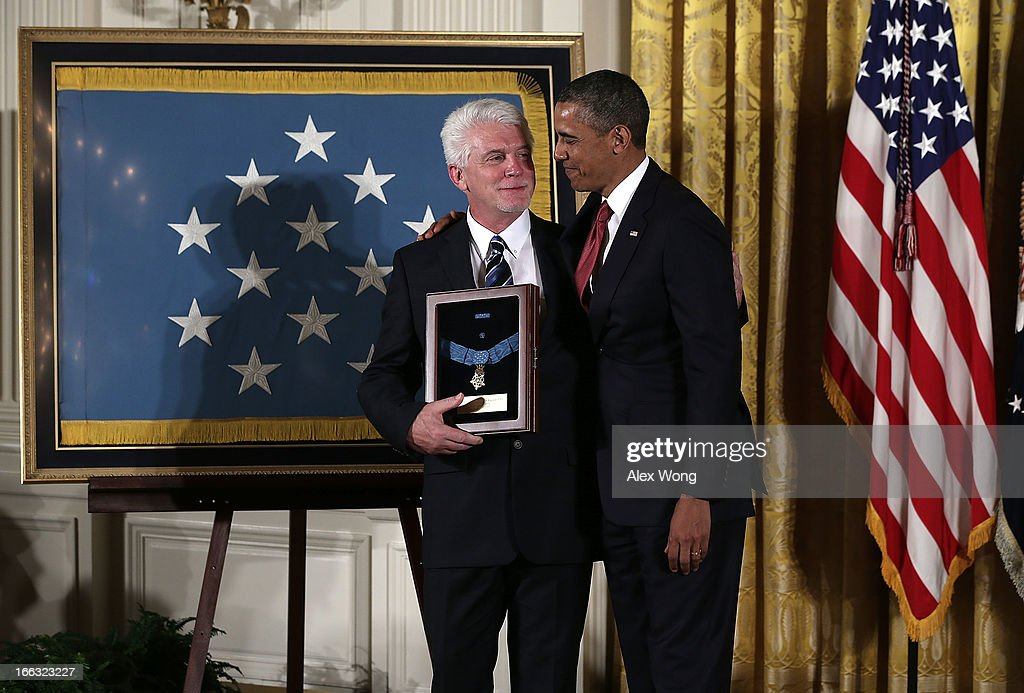 Ray Kapaun (L), nephew of U.S. Army Chaplain (Captain) Emil J. Kapaun, and U.S. President <a gi-track='captionPersonalityLinkClicked' href=/galleries/search?phrase=Barack+Obama&family=editorial&specificpeople=203260 ng-click='$event.stopPropagation()'>Barack Obama</a> (R) share a moment after he was presented with his uncle's Medal of Honor for conspicuous gallantryduring an East Room Ceremony April 11, 2013 at the White House in Washington, DC. Chaplain Kapaun received the Medal of Honor posthumously for his extraordinary heroism while serving with the 3d Battalion, 8th Cavalry Regiment, 1st Cavalry Division during combat operations against an armed enemy at Unsan, Korea and as a prisoner of war from November 1-2, 1950.