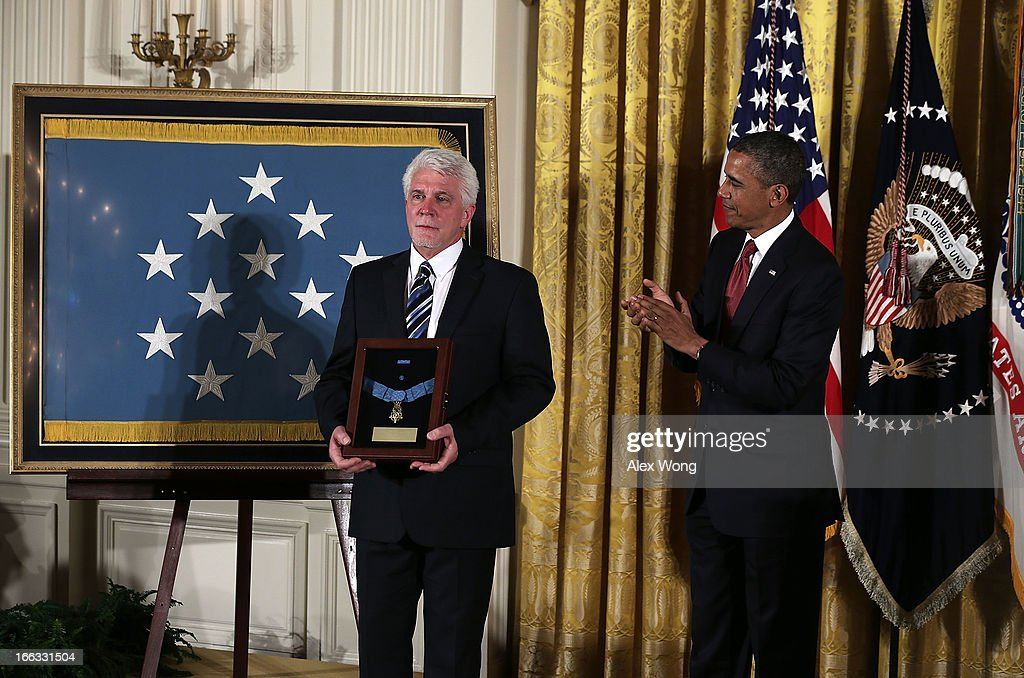Ray Kapaun (L), nephew of U.S. Army Chaplain (Captain) Emil J. Kapaun, stands on the stage after he was presented with his uncle's a Medal of Honor for conspicuous gallantry by U.S. President <a gi-track='captionPersonalityLinkClicked' href=/galleries/search?phrase=Barack+Obama&family=editorial&specificpeople=203260 ng-click='$event.stopPropagation()'>Barack Obama</a> (R) during an East Room Ceremony April 11, 2013 at the White House in Washington, DC. Chaplain Kapaun received the Medal of Honor posthumously for his extraordinary heroism while serving with the 3d Battalion, 8th Cavalry Regiment, 1st Cavalry Division during combat operations against an armed enemy at Unsan, Korea and as a prisoner of war from November 1-2, 1950.
