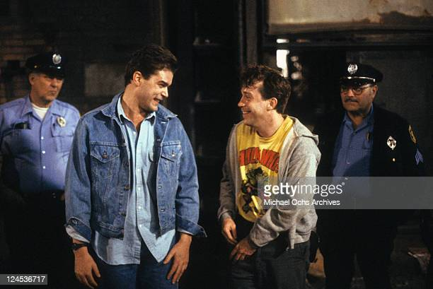 Ray Liotta and Tom Hulce laughing in front of officers in a scene from the film 'Dominick And Eugene' 1988