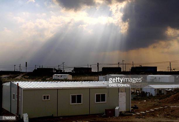 A ray of light is seen through the clouds over the caravans of the West Bank settlement of Amona north of Ramalllah 27 November 2003 Israel stuck to...