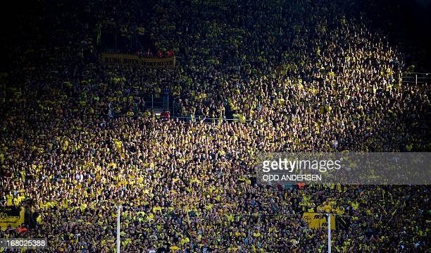 A ray of sunlight hits a section of the 'yellow Wall ' as Dortmund fans cheer on the south stand during the German first division Bundesliga football...