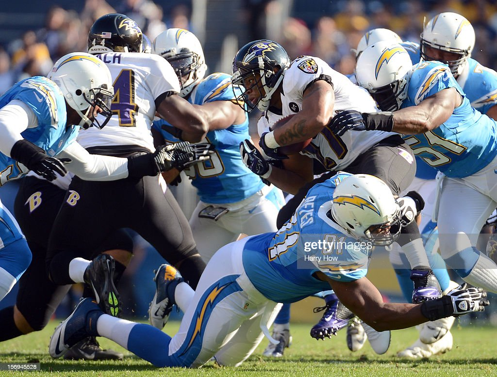Ray Rice #27 of the Baltimore Ravens is tackled by Takeo Spikes #51 and Kendall Reyes #91 of the San Diego Chargers for a stop on third down at Qualcomm Stadium on November 25, 2012 in San Diego, California.
