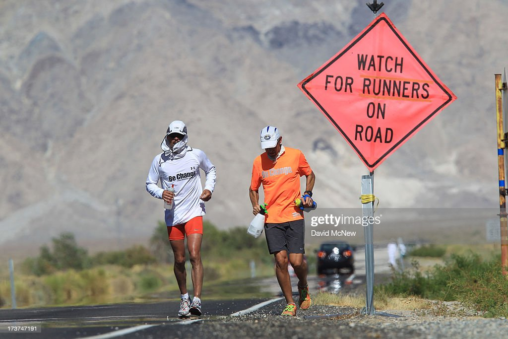 Ray Sanchez (L) of Sacramento, California runs along highway 136 north of Lake Owens as he approaches the town of Lone Pine during the AdventurCORPS Badwater 135 ultra-marathon race on July 16, 2013 outside of Death Valley National Park, California. Billed as the toughest footrace in the world, the 36th annual Badwater 135 starts at Badwater Basin in Death Valley, 280 feet below sea level, where athletes begin a 135-mile non-stop run over three mountain ranges in extreme mid-summer desert heat to finish at 8,350-foot near Mount Whitney for a total cumulative vertical ascent of 13,000 feet. July 10 marked the 100-year anniversary of the all-time hottest world record temperature of 134 degrees, set in Death Valley where the average high in July is 116. A total of 96 competitors from 22 nations are attempting the run which equals about five back-to-back marathons. Previous winners have completed all 135 miles in slightly less than 24 hours.