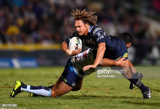 Ray Thompson of the Cowboys is tackled by Ryan James of the Titans during the round 13 NRL match between the North Queensland Cowboys and the Gold...