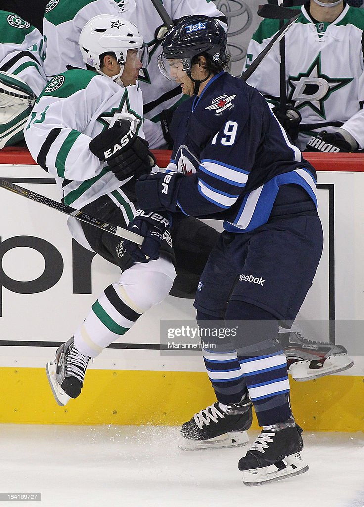 Ray Whitney #13 of the Dallas Stars is taken to the boards by Jim Slater #19 of the Winnipeg Jets in first period action of an NHL game at the MTS Centre on October 11, 2013 in Winnipeg, Manitoba, Canada.