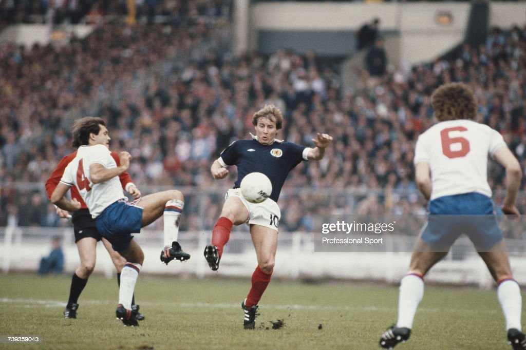 Ray Wilkins (#4) of England and Asa Hartford (#10) of Scotland both attempt to gain posession of the ball as England midfielder Bryan Robson (#6) looks on during the British Championships home international match between England and Scotland at Wembley Stadium in London on 23rd May 1981. Scotland would go on to win the game 1-0.