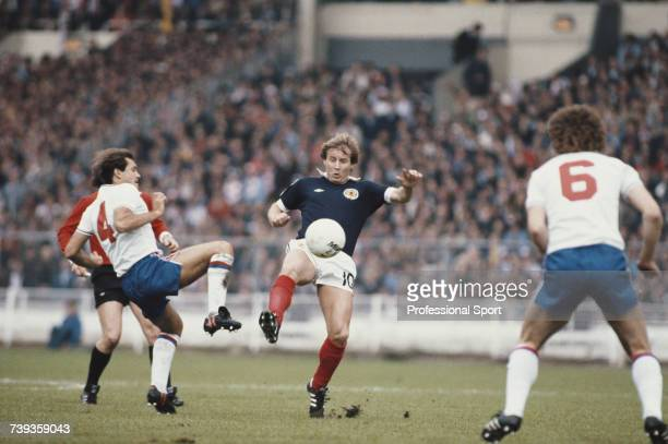 Ray Wilkins of England and Asa Hartford of Scotland both attempt to gain posession of the ball as England midfielder Bryan Robson looks on during the...