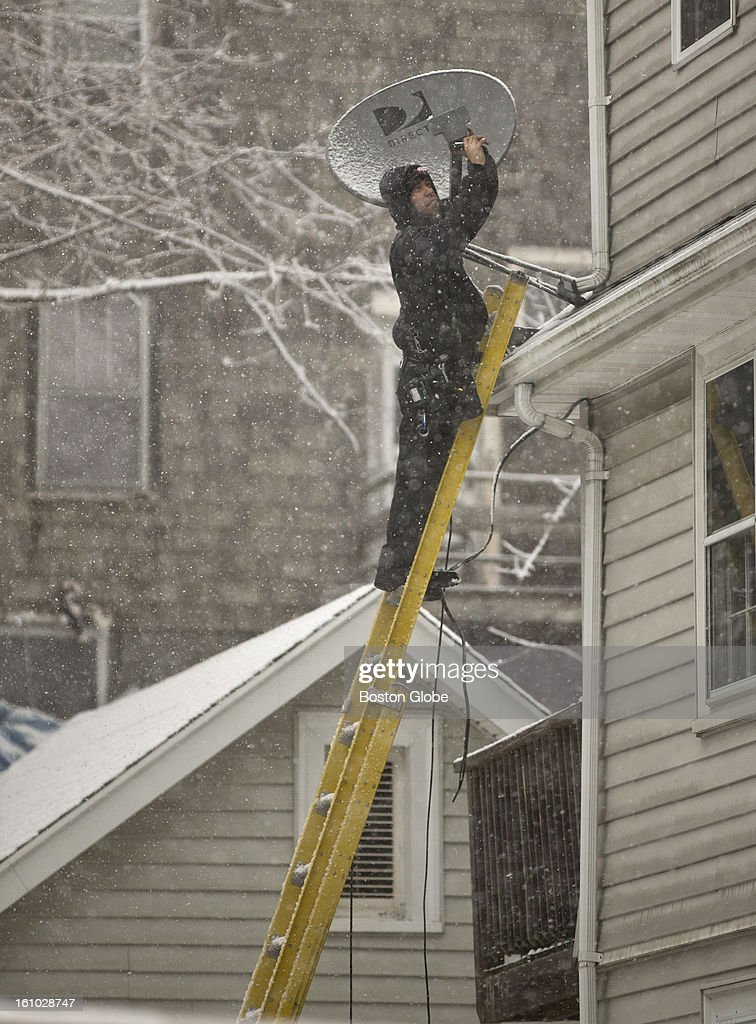Rayan Vieira from West Bridgewater installs a HD satellite dish on a second story ledge as the storm hits Quincy on Friday, Feb. 8, 2013.