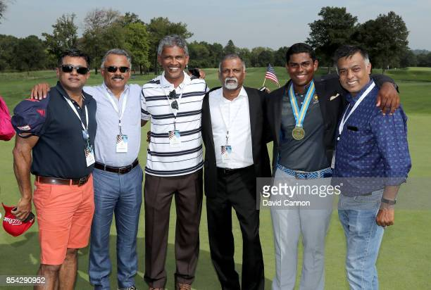 Rayhan Thomas of India and the International team poses with his medal and a number of his friends and family during the final day singles matches in...