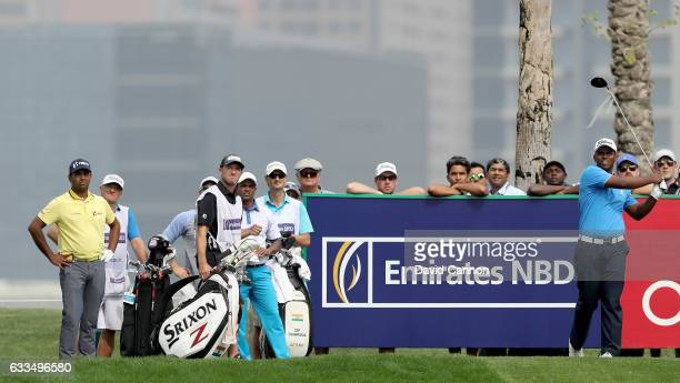 Rayhan Thomas of India plays his tee shot on the par 4 ninth hole watched by his playing partners SSPChowrasia and Anirban Lahiri of India during the...