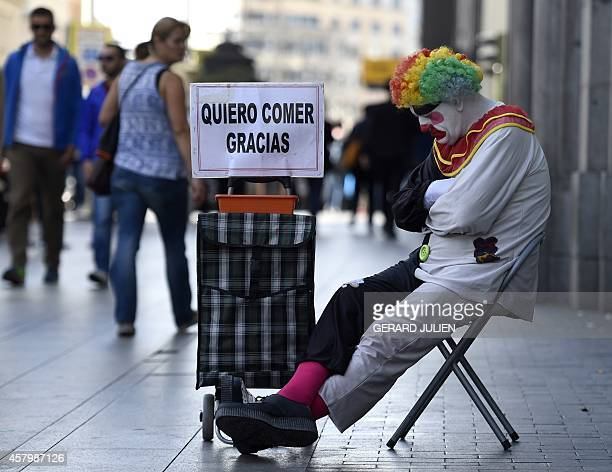 Rayito a beggar dressed as a clown sits next to a placard reading 'I want to eat thank you' in Gran Via street in the centre of Madrid on October 28...