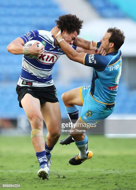 Raymond Faitala of the Bulldogs is tackled by Tyrone Roberts of the Titans during the round 25 NRL match between the Gold Coast Titans and the...