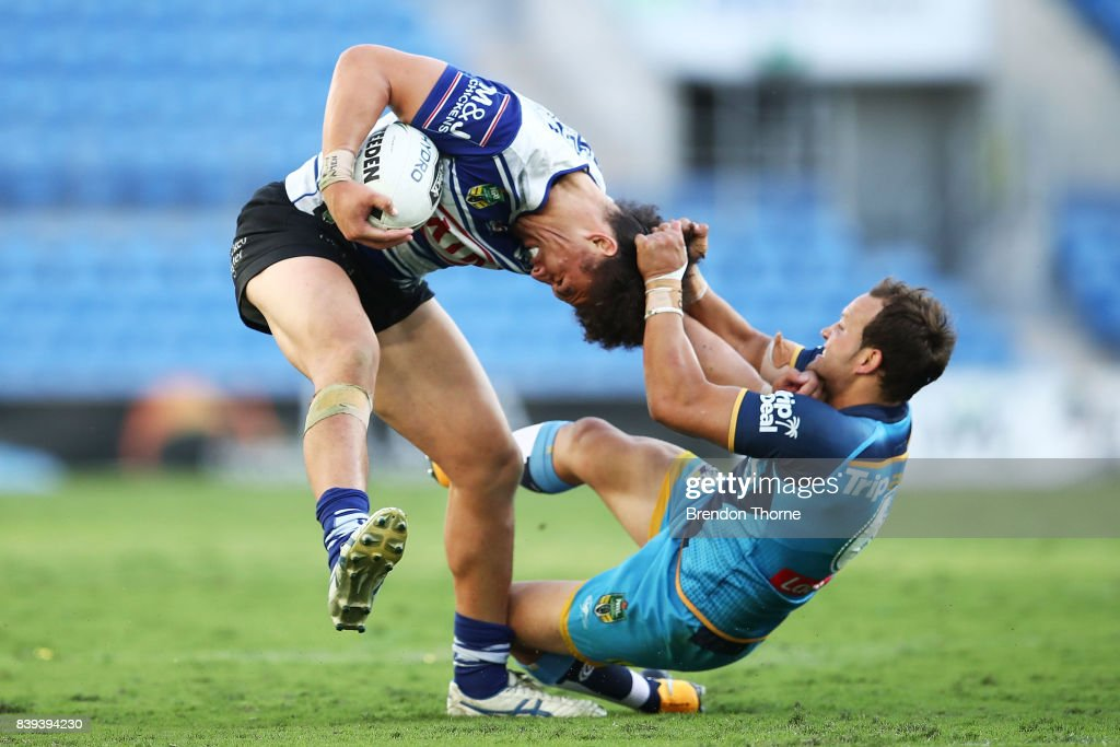 Raymond Faitala of the Bulldogs is tackled by Tyrone Roberts of the Titans during the round 25 NRL match between the Gold Coast Titans and the Canterbury Bulldogs at Cbus Super Stadium on August 26, 2017 in Gold Coast, Australia.