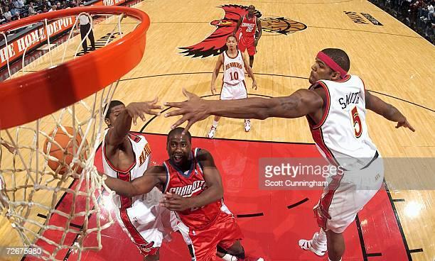 Raymond Felton of the Charlotte Bobcats drives to the basket against Josh Smith and Joe Johnson of the Atlanta Hawks on November 29 2006 at Philips...