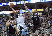 Raymond Felton of the Dallas Mavericks drives to the basket against Wayne Ellington of the Brooklyn Nets and Andrea Bargnani of the Brooklyn Nets in...