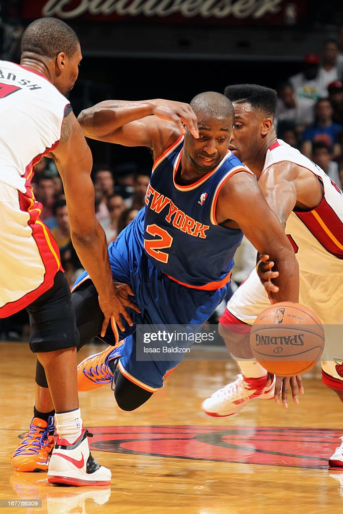 Raymond Felton #2 of the New York Knicks battles for a loose ball against Chris Bosh #1 and Norris Cole #30 of the Miami Heat on April 2, 2013 at American Airlines Arena in Miami, Florida.