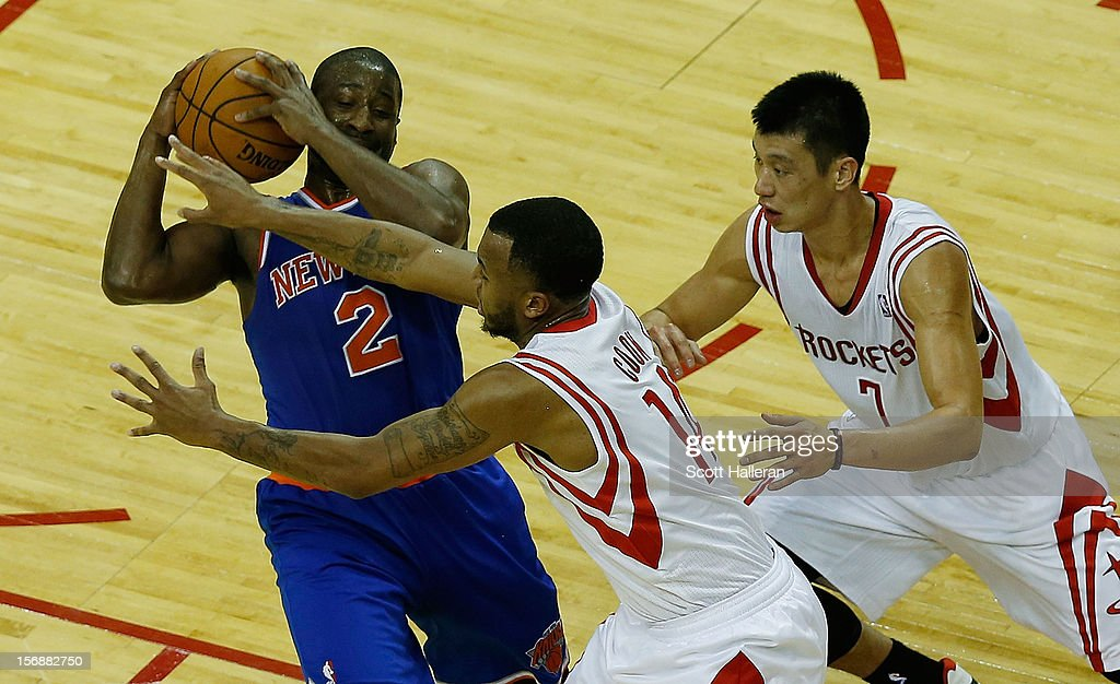 Raymond Felton #2 of the New York Knicks battles for the ball with Daequan Cook #14 and Jeremy Lin #7 of the Houston Rockets at the Toyota Center on November 23, 2012 in Houston, Texas.