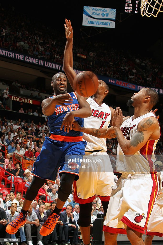 Raymond Felton #2 of the New York Knicks passes the ball against Chris Bosh #1 and Rashard Lewis #9 of the Miami Heat on April 2, 2013 at American Airlines Arena in Miami, Florida.