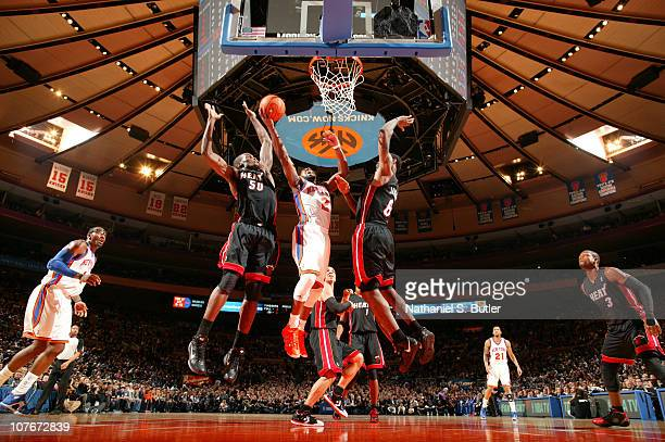 Raymond Felton of the New York Knicks shoots against Joel Anthony and LeBron James of the Miami Heat during a game on December 17 2010 at Madison...
