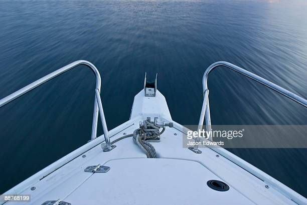 The bow of a speed boat races over the calm surface of a lake.