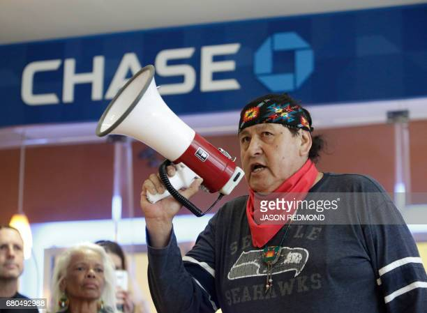 Raymond Kingfisher speaks as indigenous leaders and climate activists disrupt business at a Chase Bank branch to protest funding tar sands...