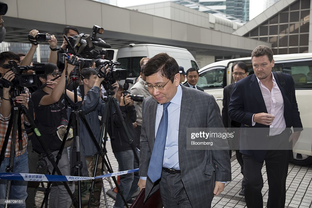 Raymond Kwok, co-chairman of Sun Hung Kai Properties Ltd., arrives at the High Court in Hong Kong, China, on Thursday, May 8, 2014. Raymond and Thomas Kwok, the billionaire brothers running Hong Kongs second-largest developer, are set to go on trial today for bribing Rafael Hui, the Chinese citys former No. 2 official. All three men have pleaded not guilty and denied all charges. Photographer: Brent Lewin/Bloomberg via Getty Images