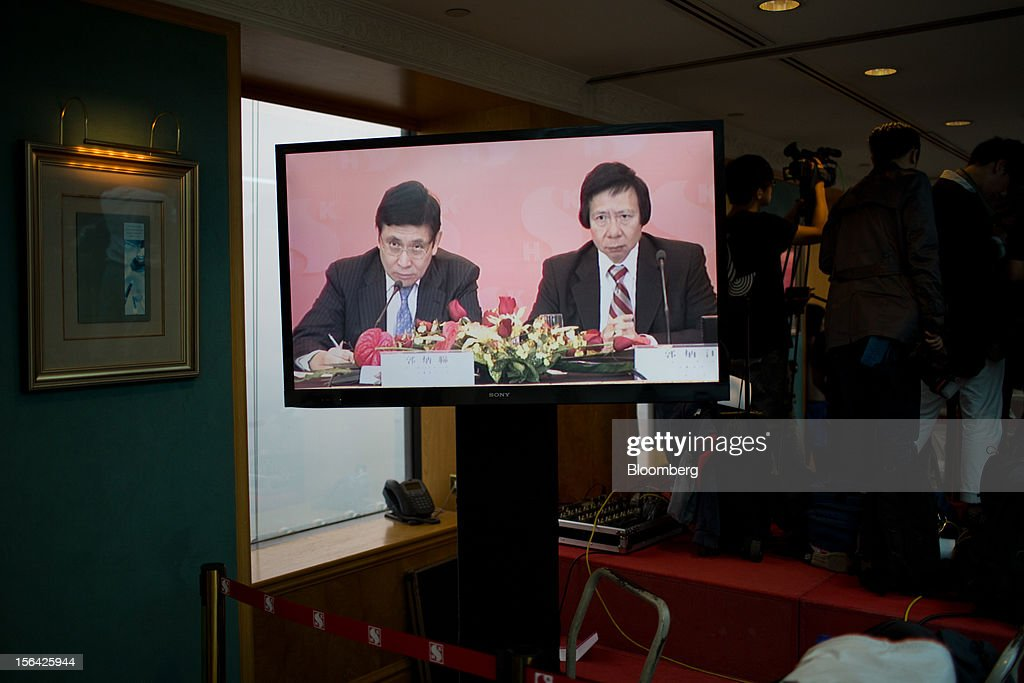 Raymond Kwok, co-chairman of Sun Hung Kai Properties Ltd., left, and Thomas Kwok, co-chairman, are displayed on a television screen during a news conference in Hong Kong, China, on Thursday, Nov. 15, 2012. Sun Hung Kai will continue buying land in Hong Kong, says Thomas Kwok. Photographer: Lam Yik Fei/Bloomberg via Getty Images