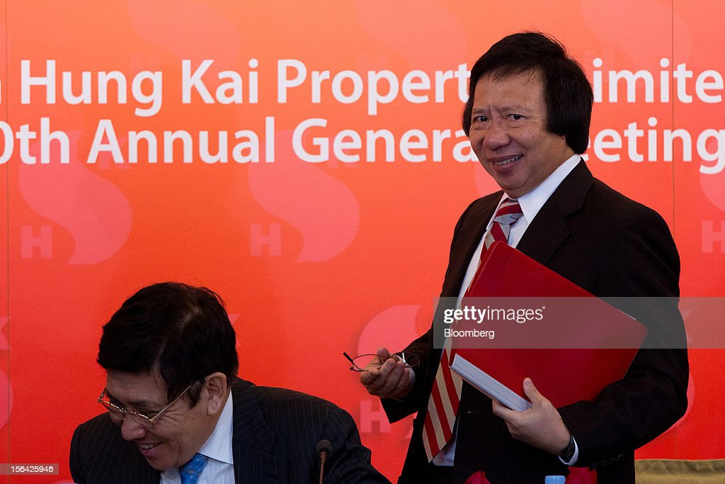 Raymond Kwok, co-chairman of Sun Hung Kai Properties Ltd., left, and Thomas Kwok, co-chairman, laugh at the end of a news conference in Hong Kong, China, on Thursday, Nov. 15, 2012. Sun Hung Kai will continue buying land in Hong Kong, says Thomas Kwok. Photographer: Lam Yik Fei/Bloomberg via Getty Images