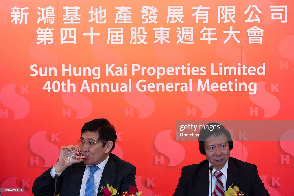 Raymond Kwok, co-chairman of Sun Hung Kai Properties Ltd., left, drinks water while Thomas Kwok, co-chairman, looks on during a news conference in Hong Kong, China, on Thursday, Nov. 15, 2012. Sun Hung Kai will continue buying land in Hong Kong, says Thomas Kwok. Photographer: Lam Yik Fei/Bloomberg via Getty Images