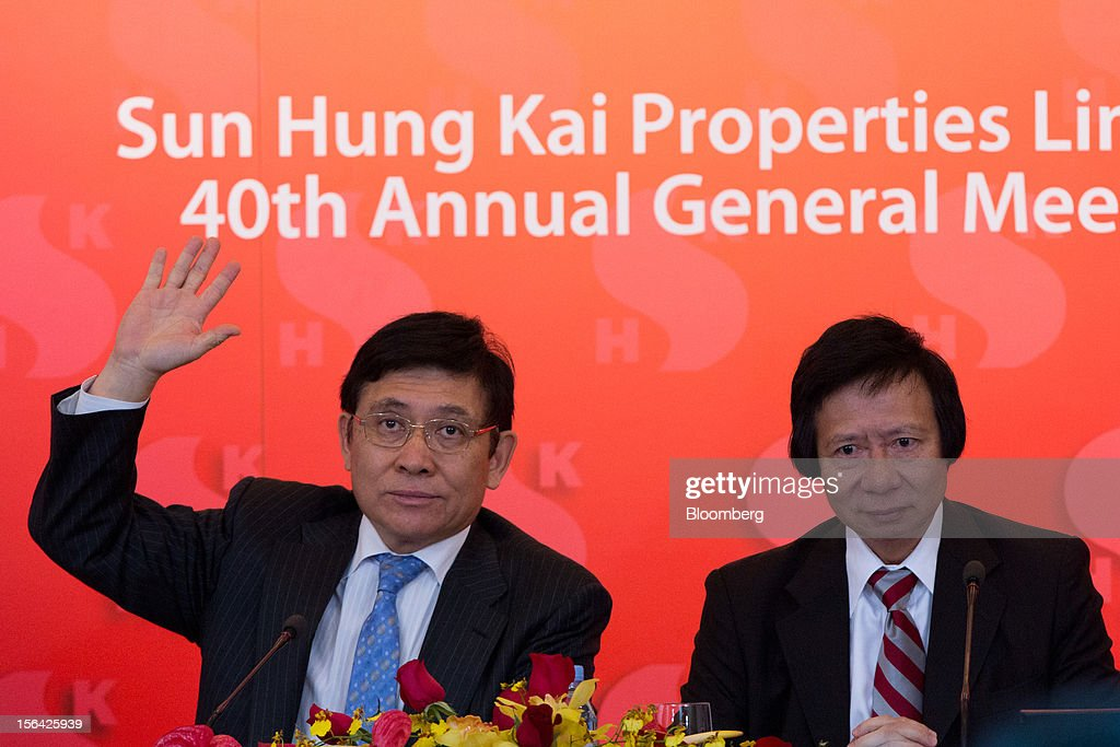 Raymond Kwok, co-chairman of Sun Hung Kai Properties Ltd., left, raises his hand while Thomas Kwok, co-chairman, looks on during a news conference in Hong Kong, China, on Thursday, Nov. 15, 2012. Sun Hung Kai will continue buying land in Hong Kong, says Thomas Kwok. Photographer: Lam Yik Fei/Bloomberg via Getty Images
