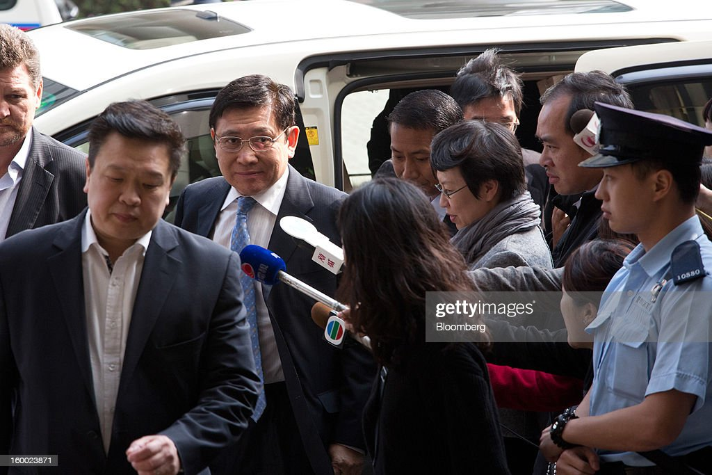 Raymond Kwok, co-chairman of Sun Hung Kai Properties Ltd., third left, arrives at the Eastern Magistrates' Court in Hong Kong, China, on Friday, Jan. 25, 2013. The prosecution's bribery case against Sun Hung Kai's billionaire co-chairmen Thomas and Raymond Kwok and Hong Kong's former No. 2 official Rafael Hui will be ready by March, a court was told. Photographer: Lam Yik Fei/Bloomberg via Getty Images