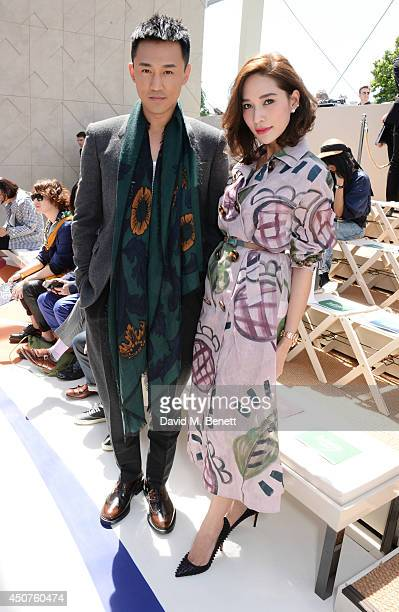 Raymond Lam and Laila Boonyasak attends the front row at Burberry Prorsum SS15 during London Collections Men at Kensington Gardens on June 17 2014 in...