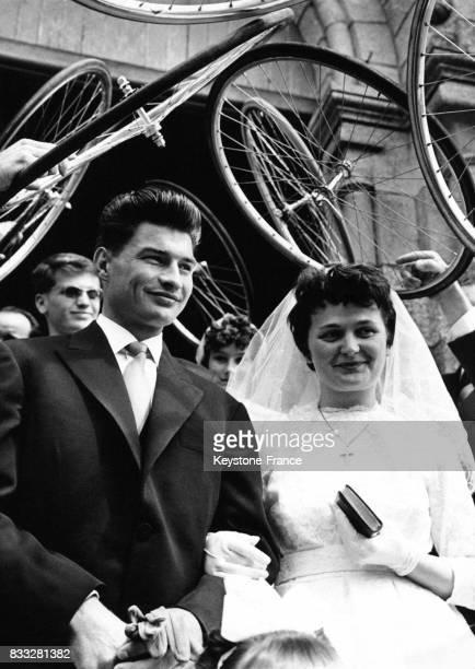 Raymond Poulidor et sa femme passent sous une voûte formée par des roues de vélos à leur sortie de l'église à Limoges France le 19 avril 1961