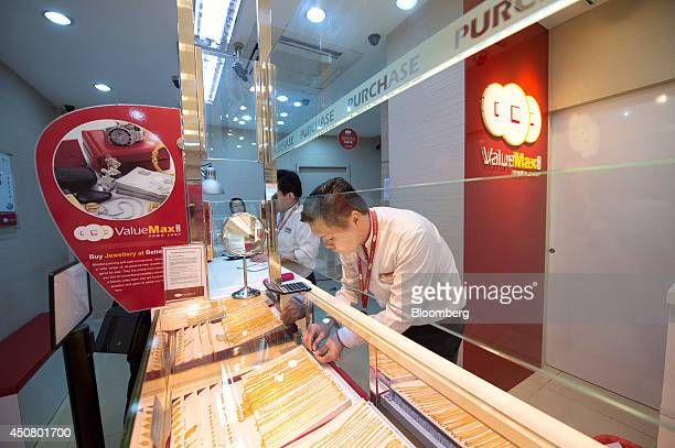 Raymond Soh an employee at ValueMax Group Ltd arranges gold necklaces in a display cabinet at one of the company's pawnshops in Singapore on...