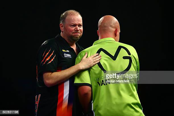 Raymond van Barneveld of Holland shakes hands with Michael van Gerwen of Holland after victory in their third round match on Day Eleven of the 2016...
