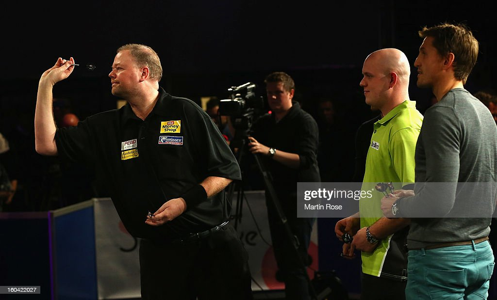 Raymond van Barneveld of Netherlands in action during a dart show tournament at between team Netherlands and Hamburger SV at Imtech Arena on January 31, 2013 in Hamburg, Germany.