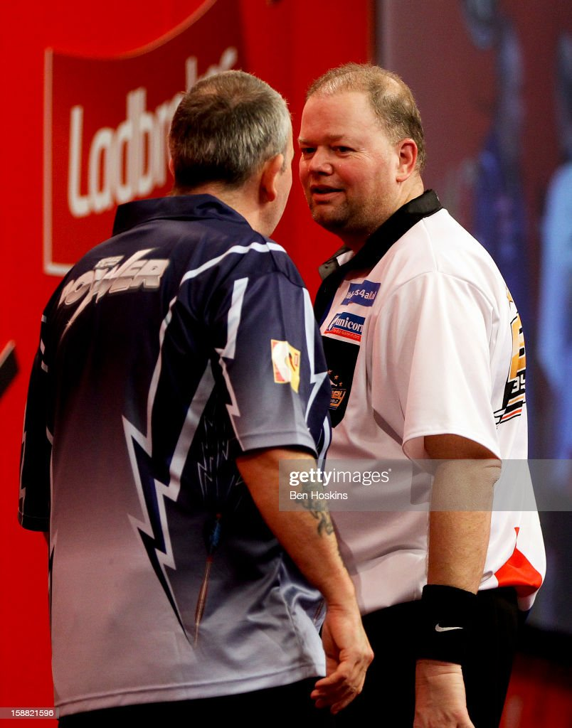 <a gi-track='captionPersonalityLinkClicked' href=/galleries/search?phrase=Raymond+van+Barneveld&family=editorial&specificpeople=2628450 ng-click='$event.stopPropagation()'>Raymond van Barneveld</a> of the Netherlands and Phil Taylor of England clash during their semi final match on day fourteen of the 2013 Ladbrokes.com World Darts Championship at the Alexandra Palace on December 30, 2012 in London, England.