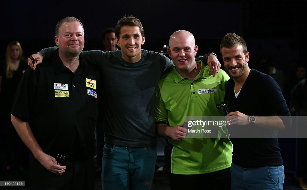 Raymond van Barneveld, Rene Adler, <a gi-track='captionPersonalityLinkClicked' href=/galleries/search?phrase=Michael+van+Gerwen&family=editorial&specificpeople=4754172 ng-click='$event.stopPropagation()'>Michael van Gerwen</a> and Rafael van der Vaart pose for a photo during a dart show tournament at between team Netherlands and Hamburger SV at Imtech Arena on January 31, 2013 in Hamburg, Germany.