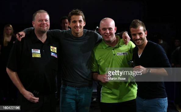 Raymond van Barneveld Rene Adler Michael van Gerwen and Rafael van der Vaart pose for a photo during a dart show tournament at between team...