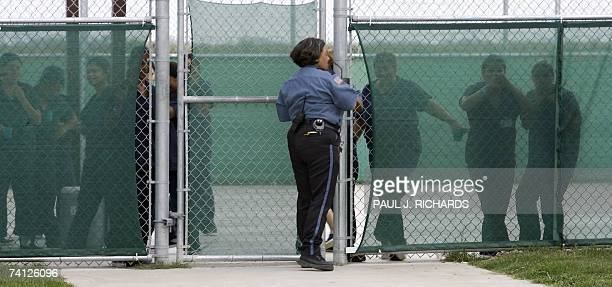A guard secures the gate as female detainees stand in the exercise yard inside Homeland Security's Willacy Detention Center a facility with 10 giant...